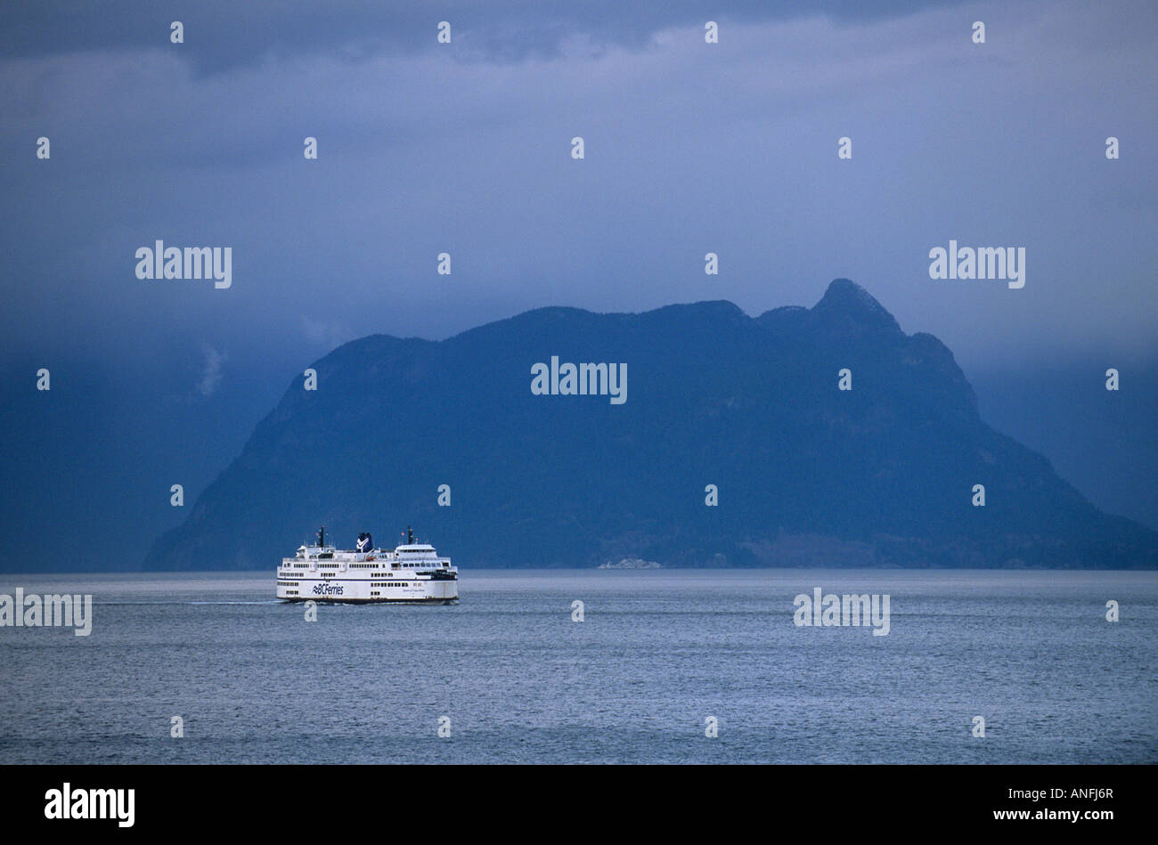 A BC Ferry crosses the Strait of Georgia under a menacing sky, british columbia, canada. - Stock Image