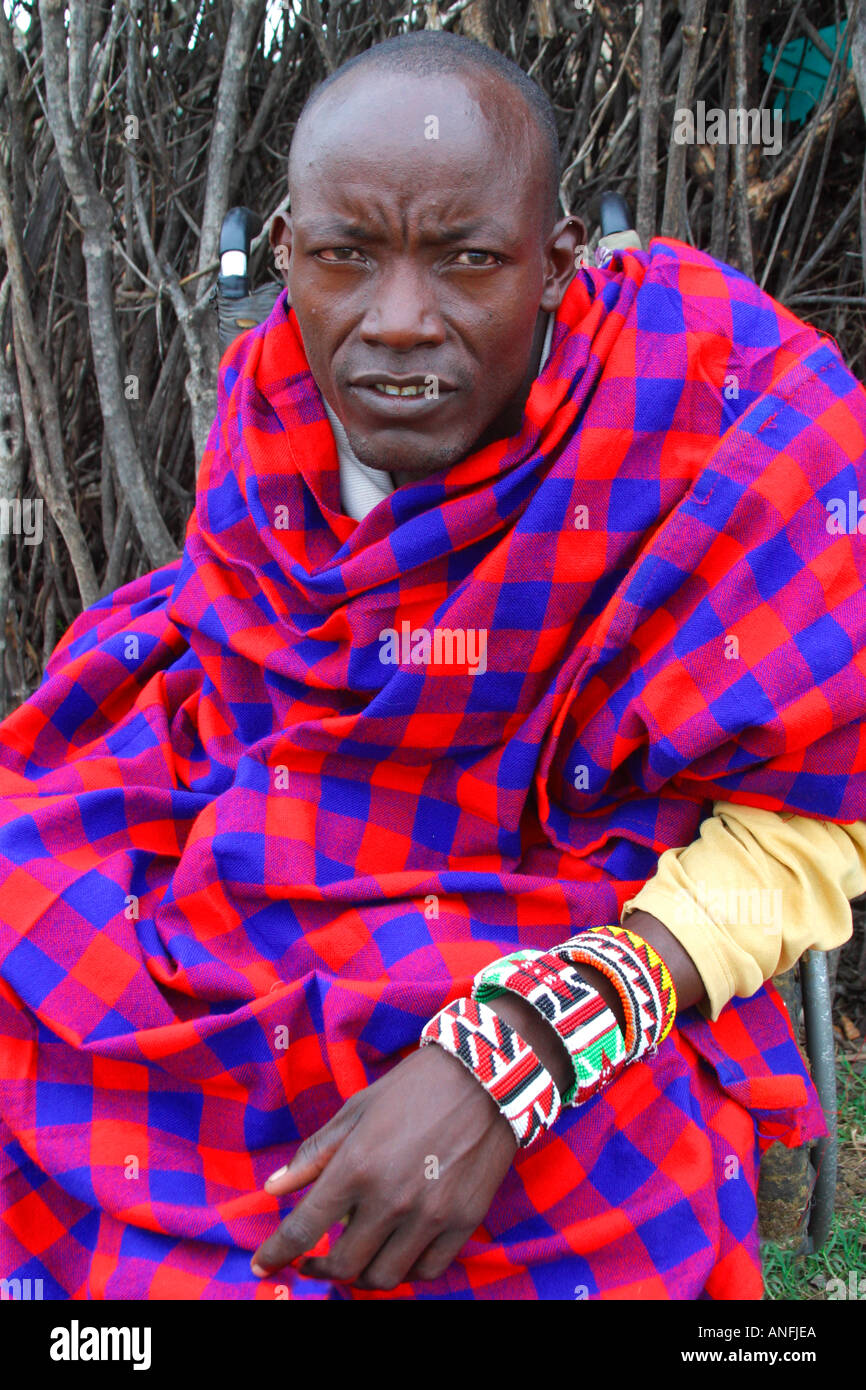 Maasai man who suffered polio as a child in wheelchair with traditional blanket Masai Mara Kenya East Africa - Stock Image