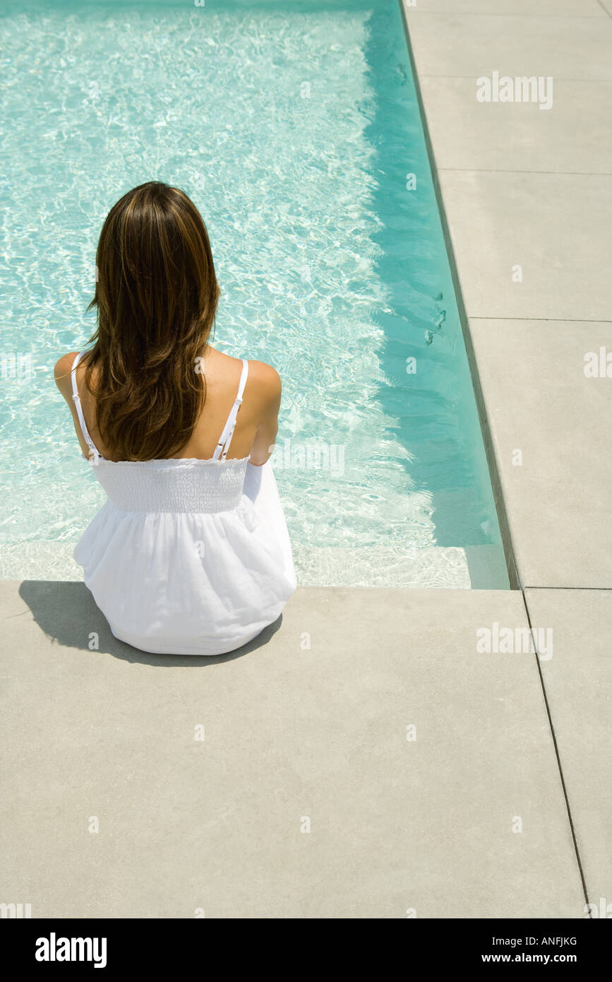 Woman sitting on edge of pool, rear view - Stock Image