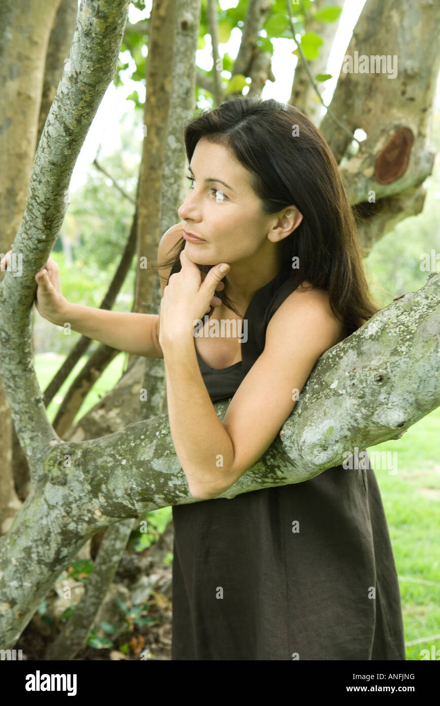 Woman standing between tree branches, leaning on branch, looking away - Stock Image