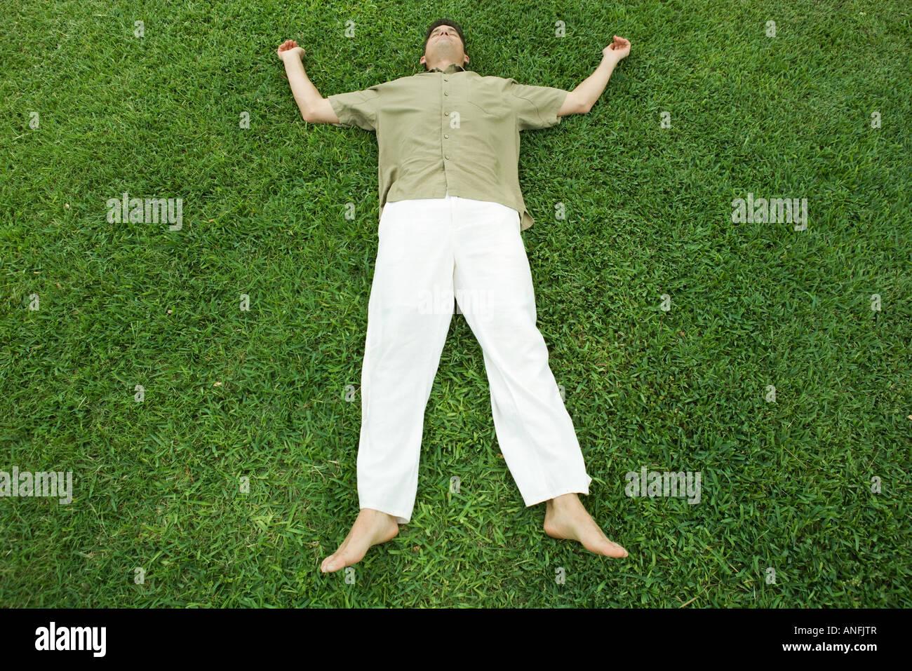 Man lying on grass, full length - Stock Image