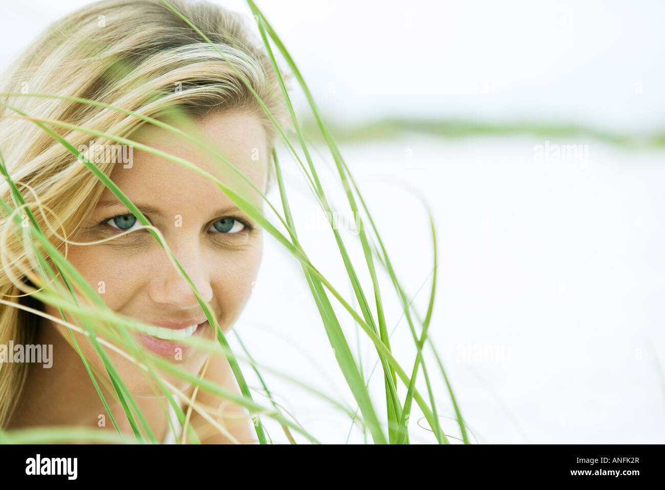 Woman looking through grass, close-up - Stock Image