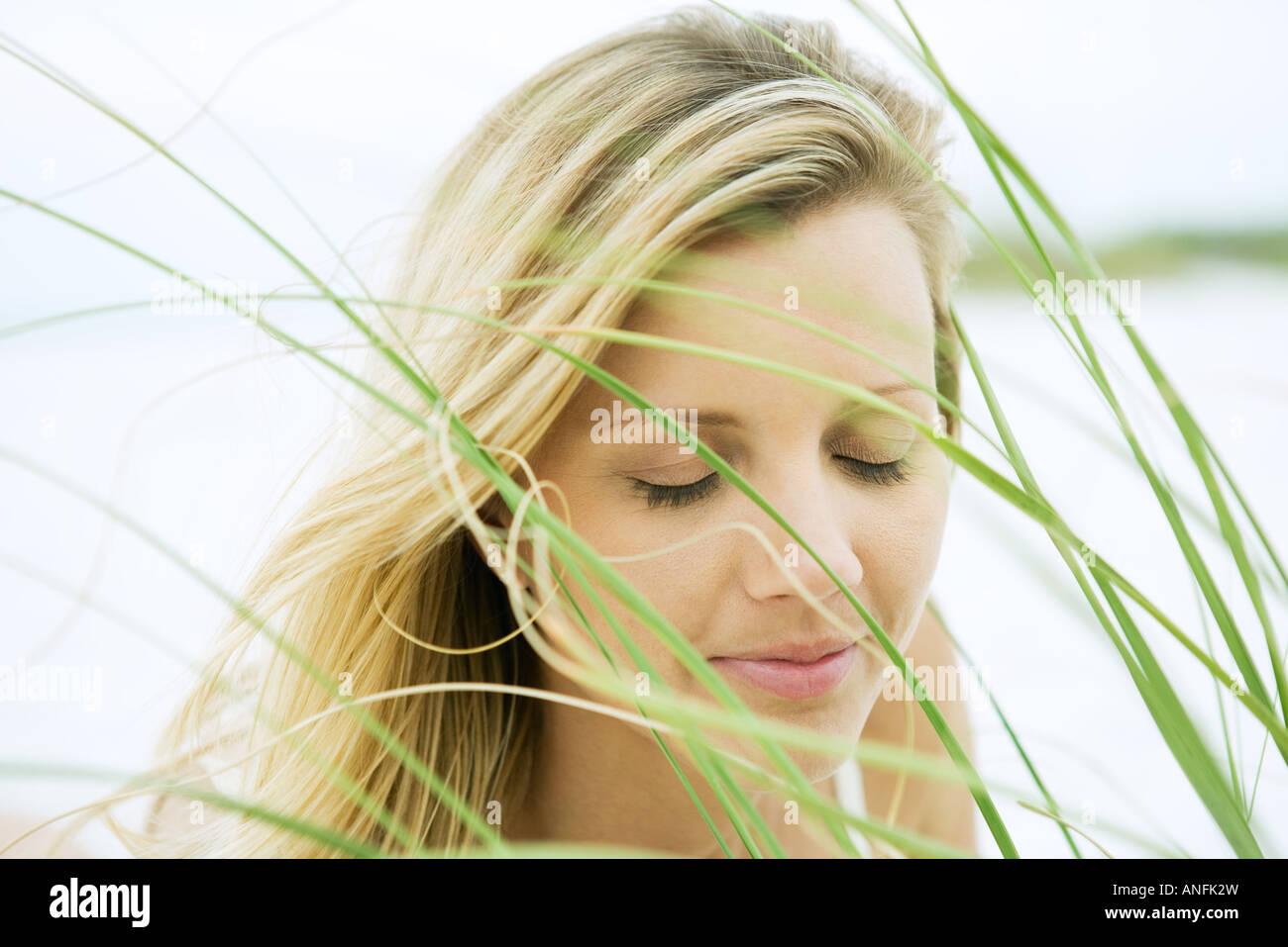 Woman closing eyes, seen through grass, close-up - Stock Image