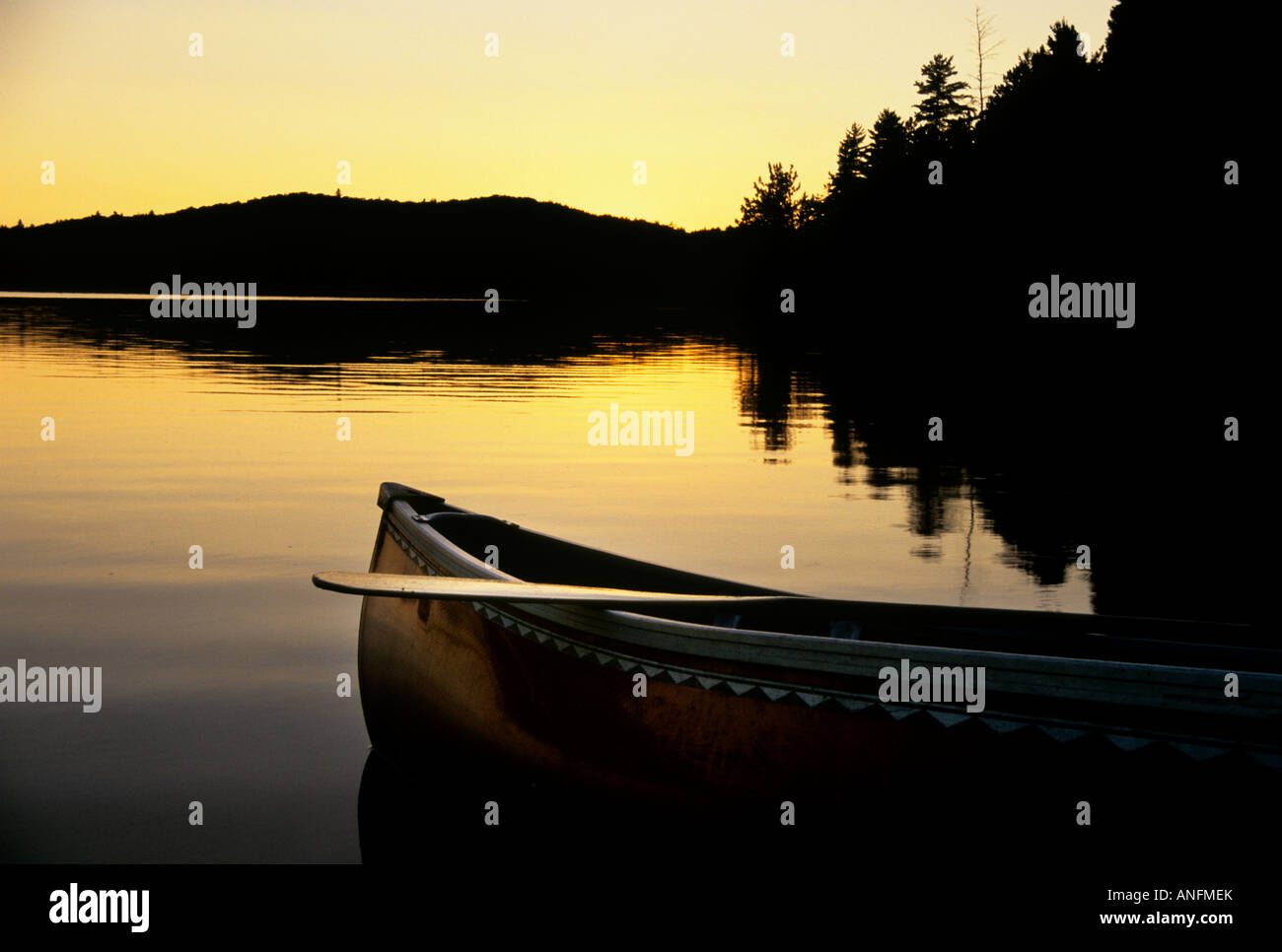 The sillhouette of a canoe as it rests on the shore of a lake at sunset on Booth Lake in Alqonguin Provincial Park, - Stock Image