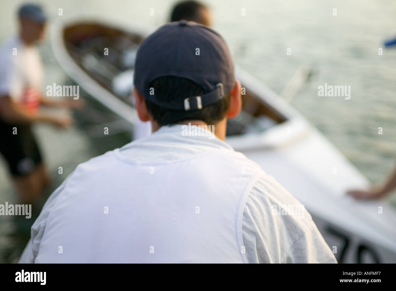 Rowers placing boat onshore - Stock Image