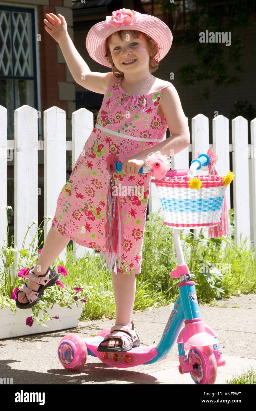 5 Year Old Girl With Sundress And Hat Standing On Scooter Canada