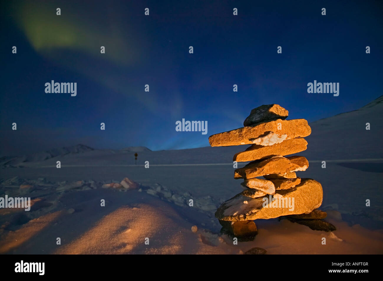 Inukshuk on Chandalar Shelf in winter with Northern Light, Aurora Borealis in background. Northern Canada. - Stock Image