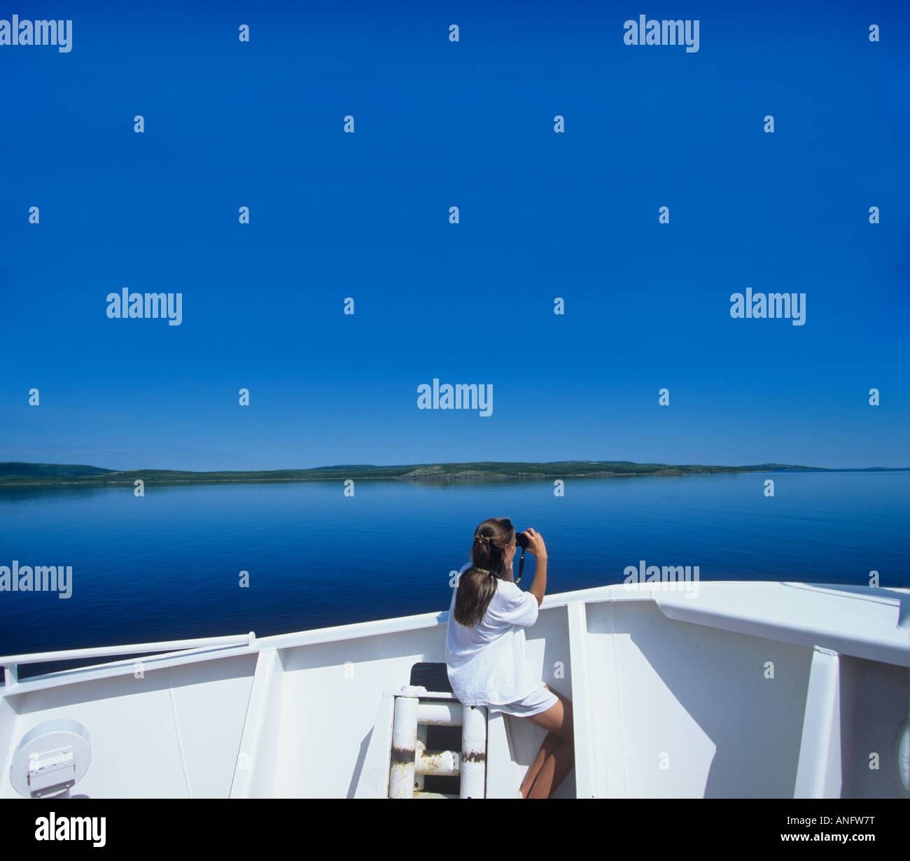 Young girl Birdwatching on deck of Coastal Boat, Cartwright, Labrador, Canada. Stock Photo