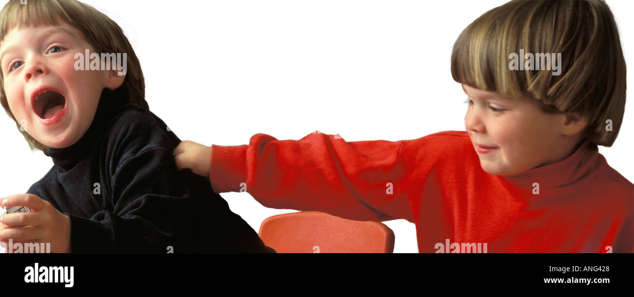 Uncontrollable hyperactive male twinsActing out  playing and pinching on a white background - Stock Image
