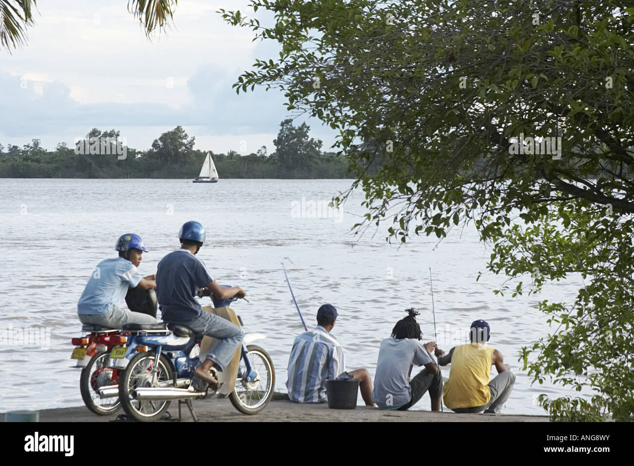 Local residents of mixed descent African and Javanese on the shore of the Suriname River - Stock Image