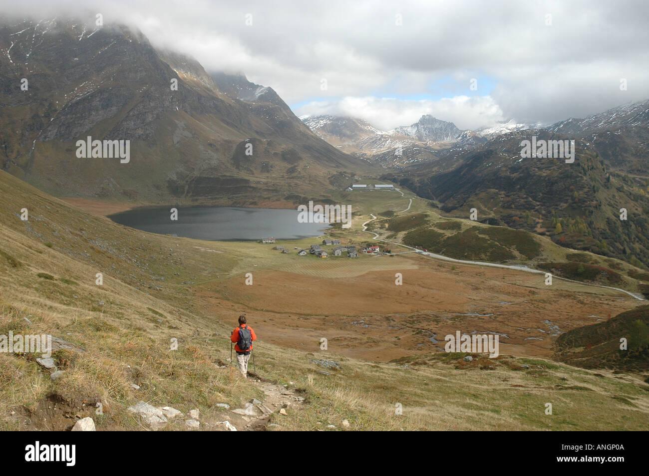 Hiker at Cadagno di Fuori Lago Cadagno Alpe di Piora Piz Corandori in fog Ritom Autumn Canton Ticino Tessin Alps Stock Photo