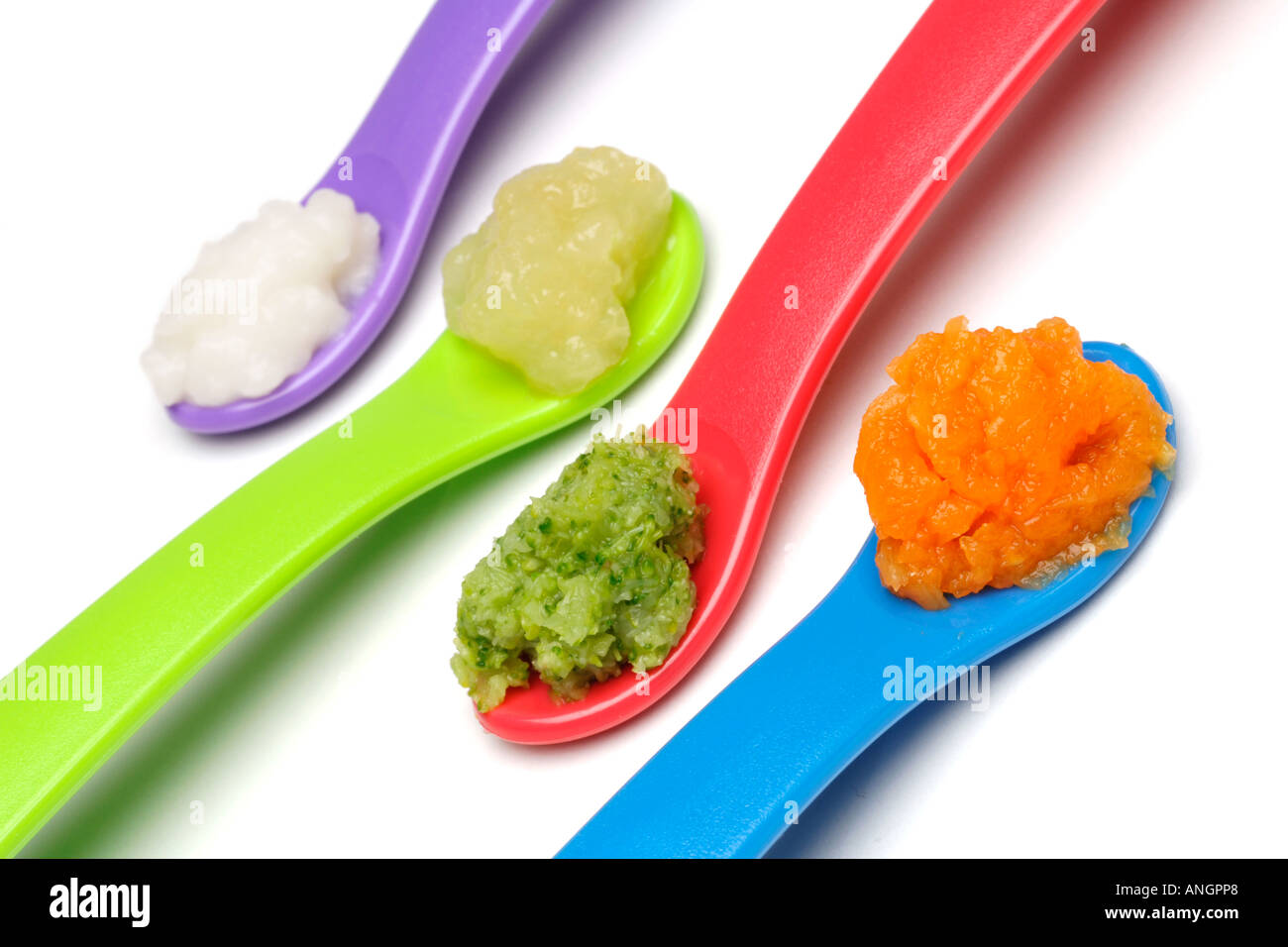 Early weaning foods for babies baby rice pureed apple broccoli carrot on plastic weaning spoons - Stock Image