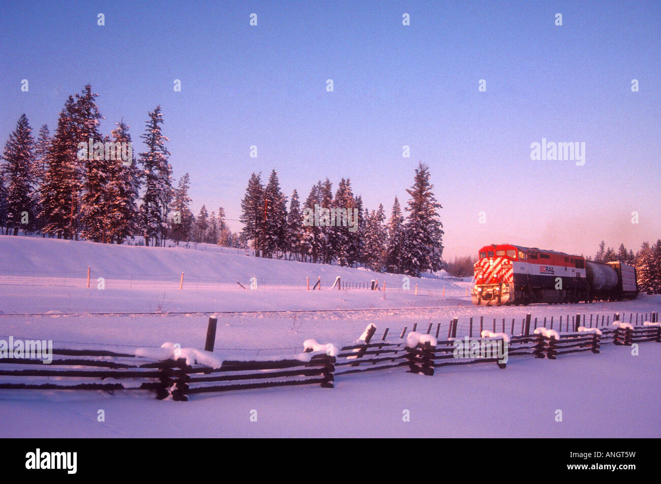 BC Rail freight train travels through central BC at sunset, British Columbia, Canada. - Stock Image
