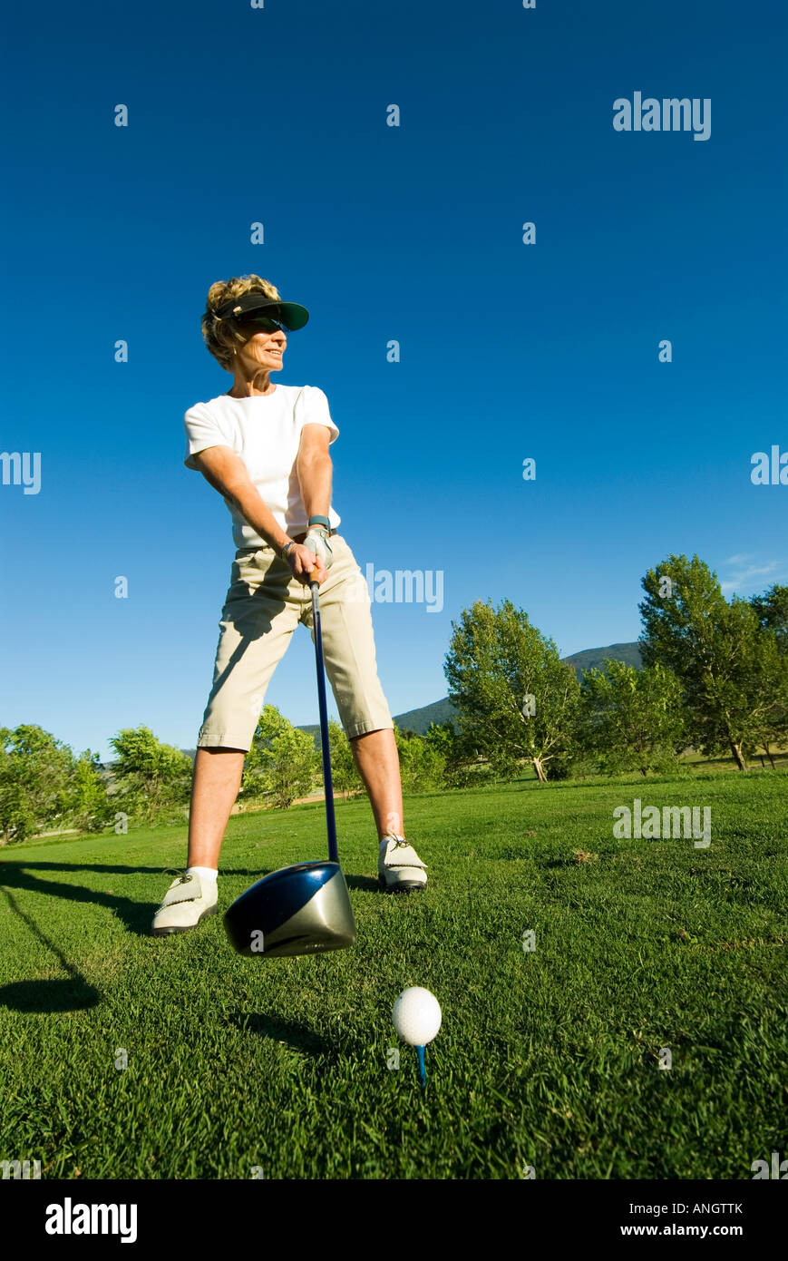 A women golfer gets ready to tee off on a course near Kamloops, British Columbia, Canada. - Stock Image