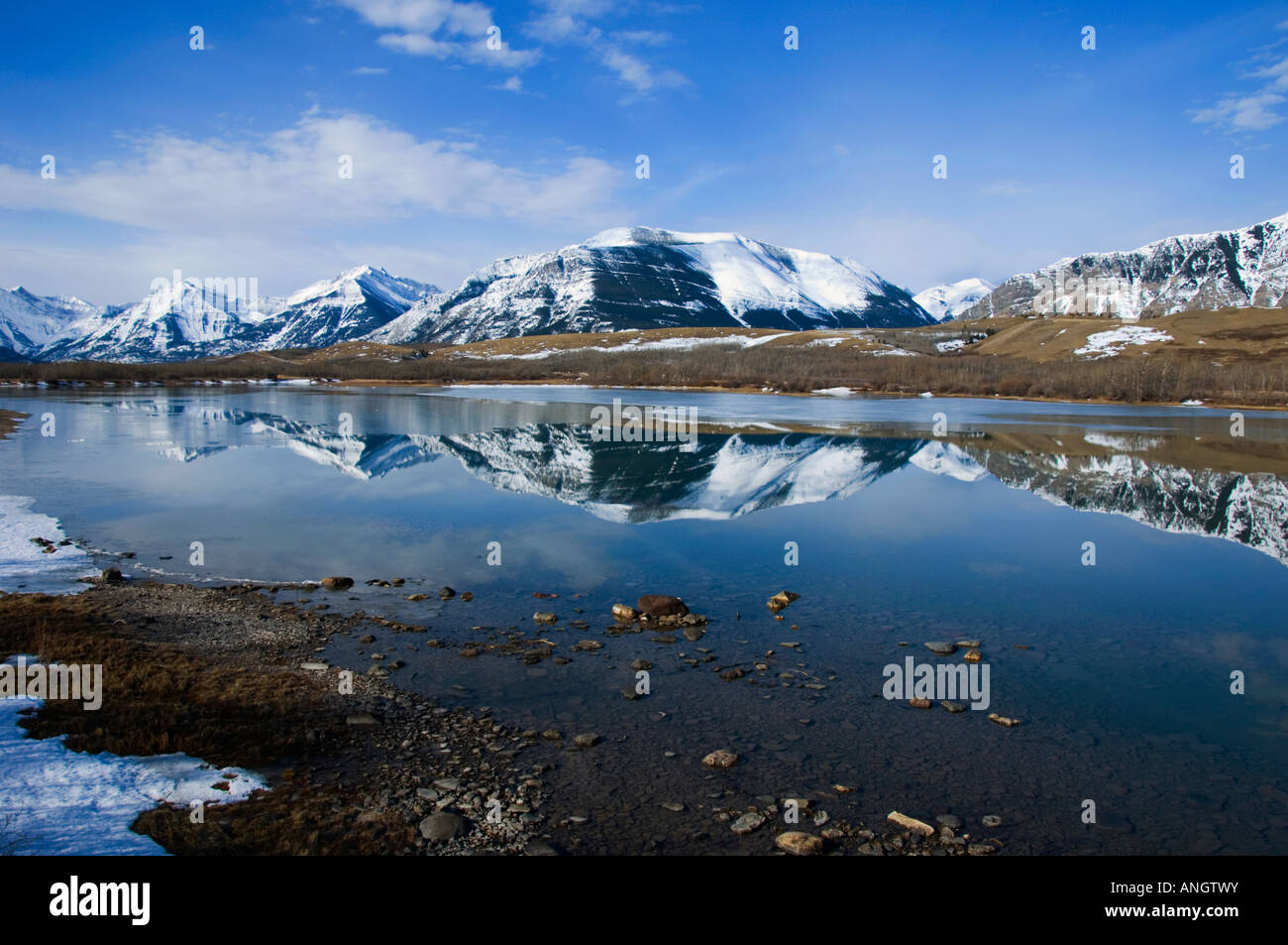 Reflection of area Mountains. Until the snowpac begins to melt the water level is down exposing gravel along the - Stock Image