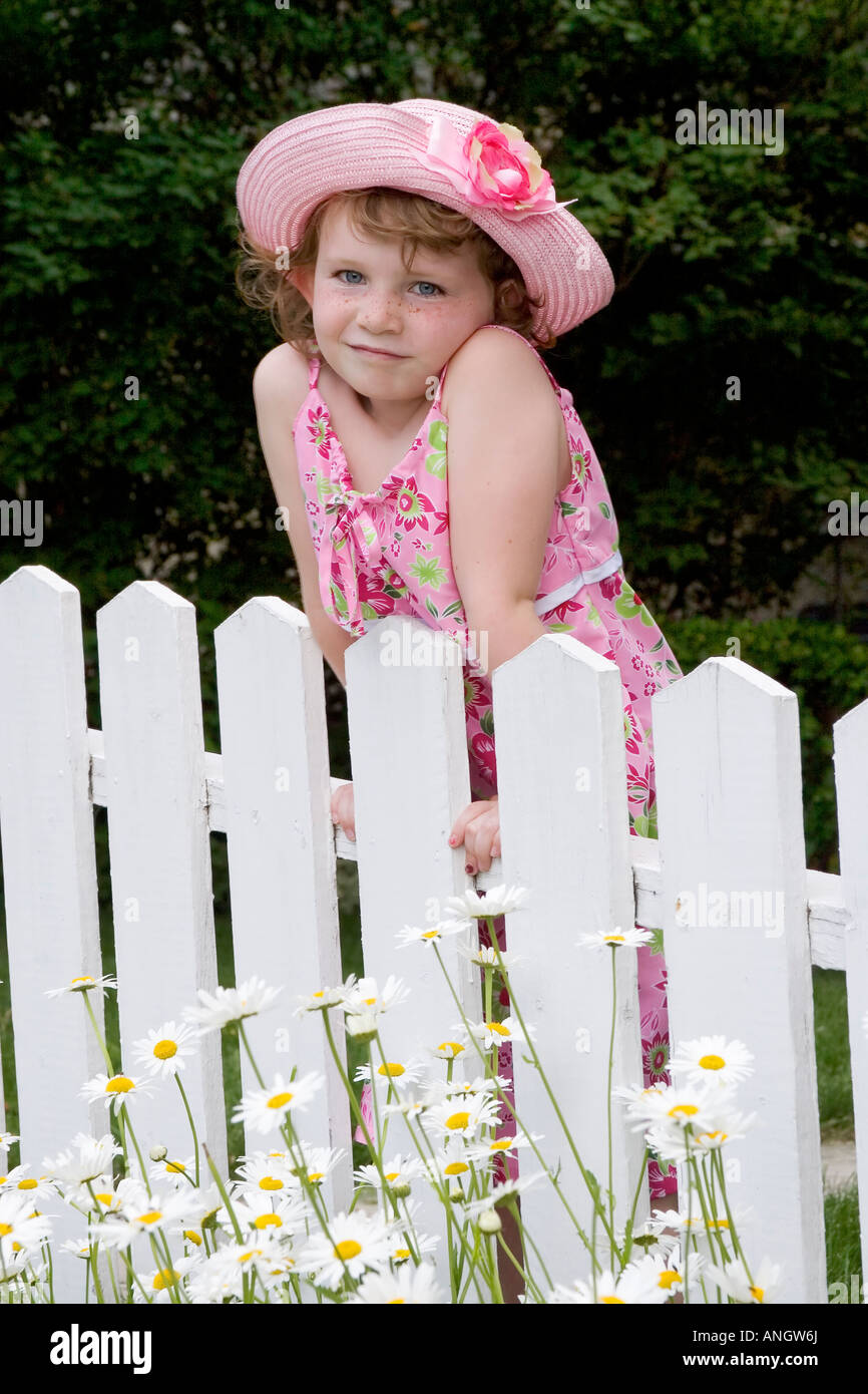 5 year old girl with sundress and hat standing in front of picket fence, Canada. - Stock Image