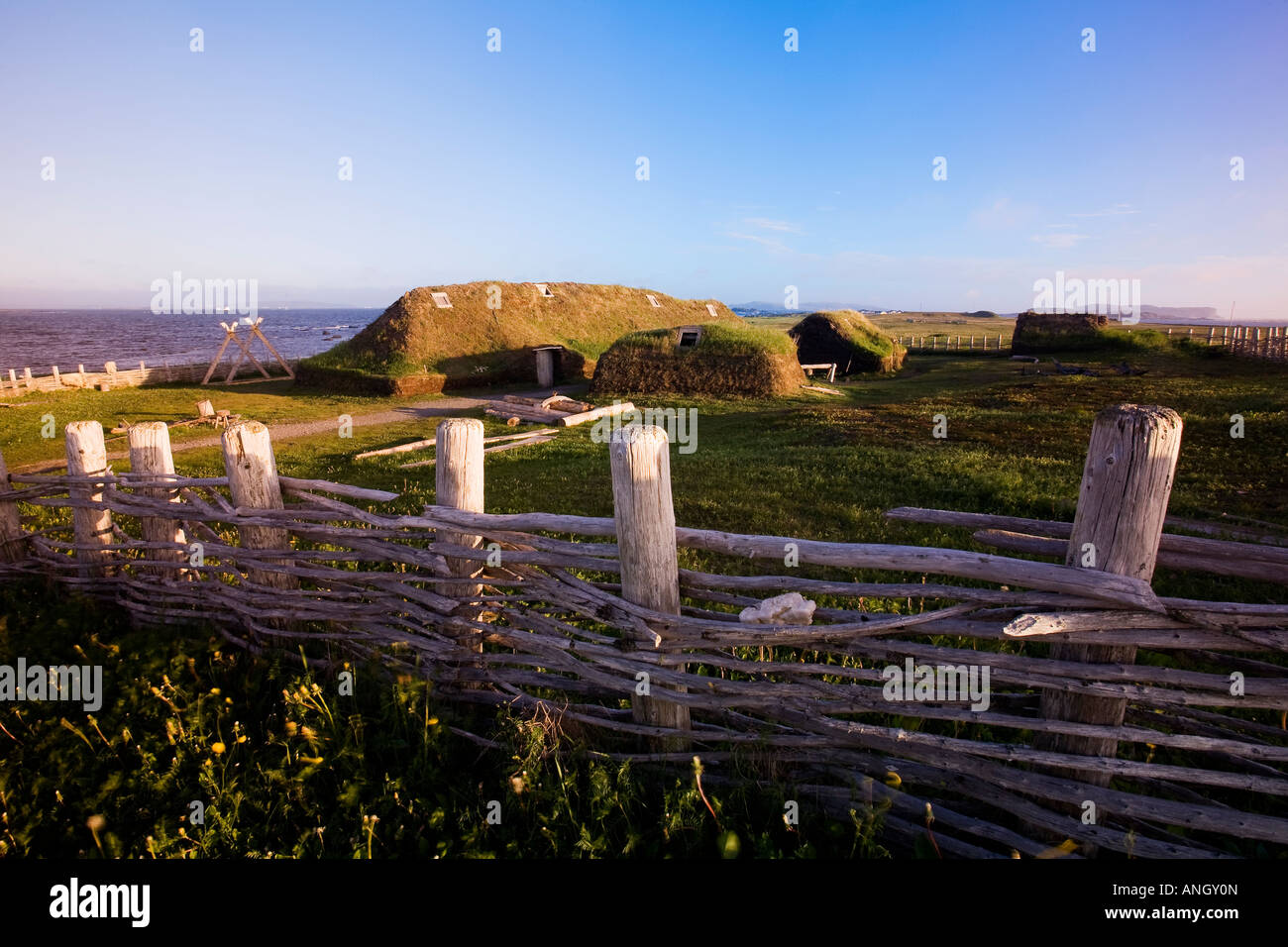 Fence and reconstructed Norse buildings at the L'Anse aux Meadows National Historic Site of Canada, Newfoundland - Stock Image