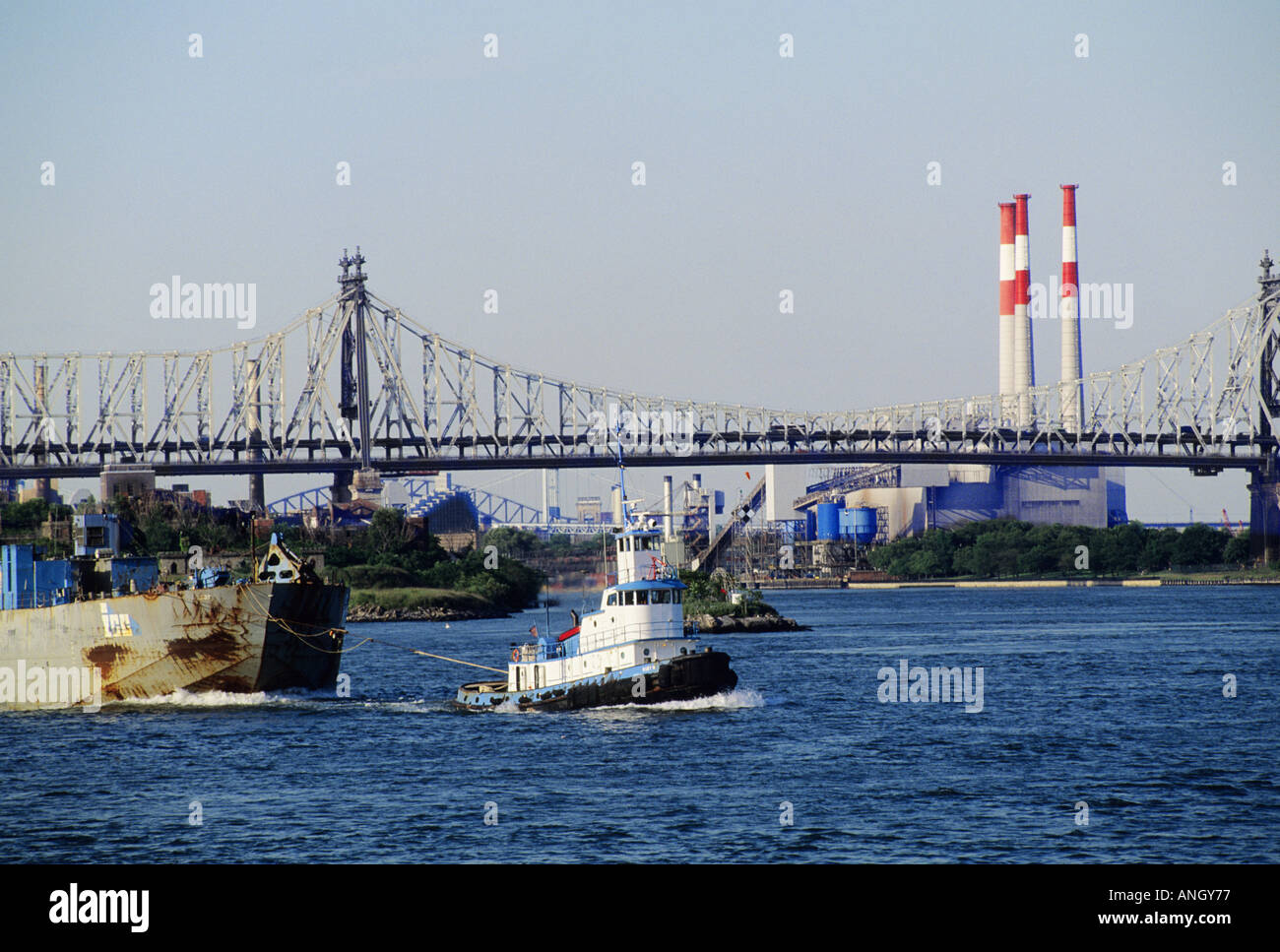 New York East River Tugboat Pulling Scow Manhattan Bridge and Con Edison Electricity Plant in Background USA - Stock Image