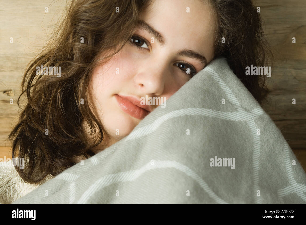 Teen girl holding blanket up to face, looking at camera, portrait