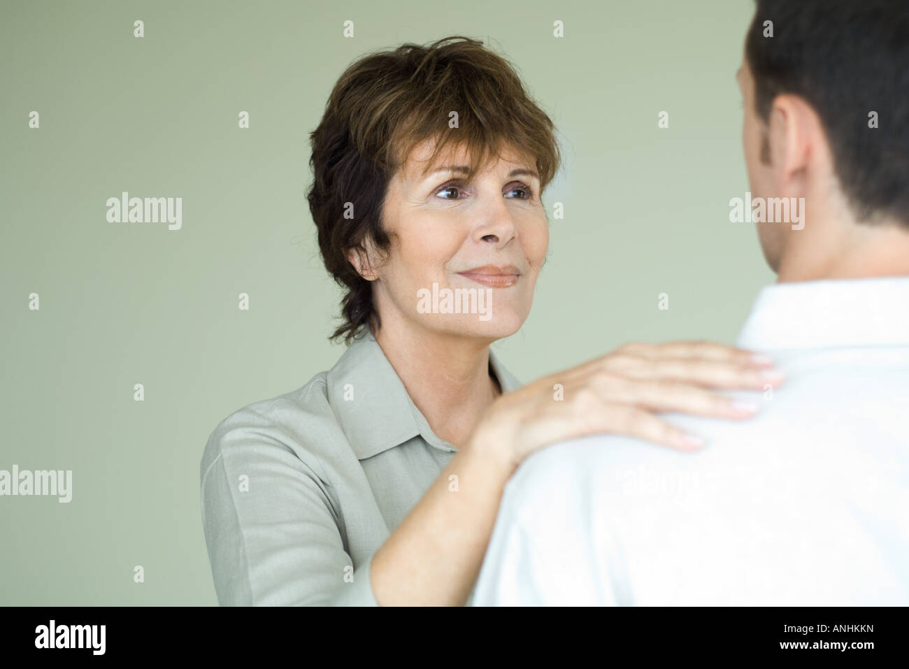 Senior woman standing in front of adult son with her hand on his shoulder, smiling - Stock Image