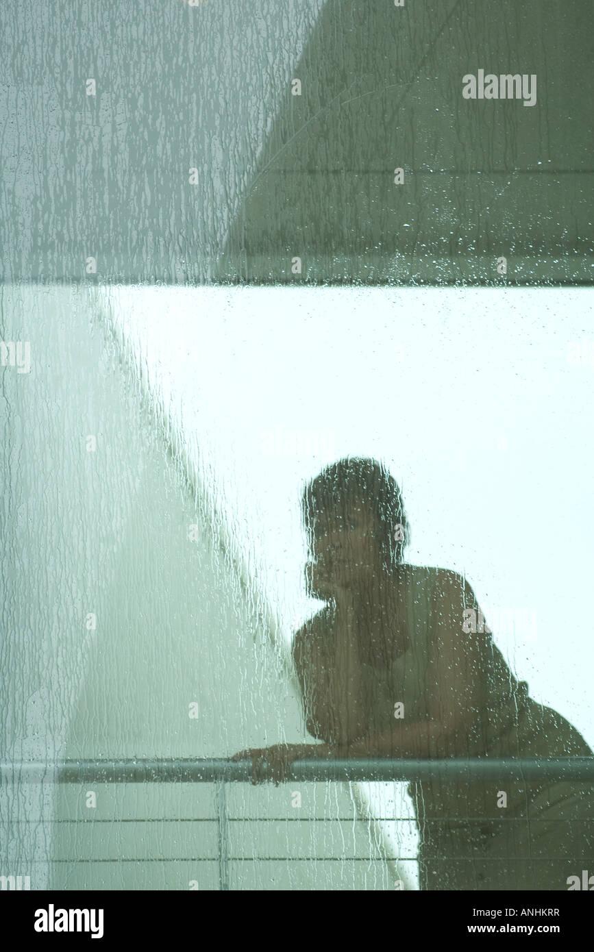 Woman looking through window in rain Stock Photo