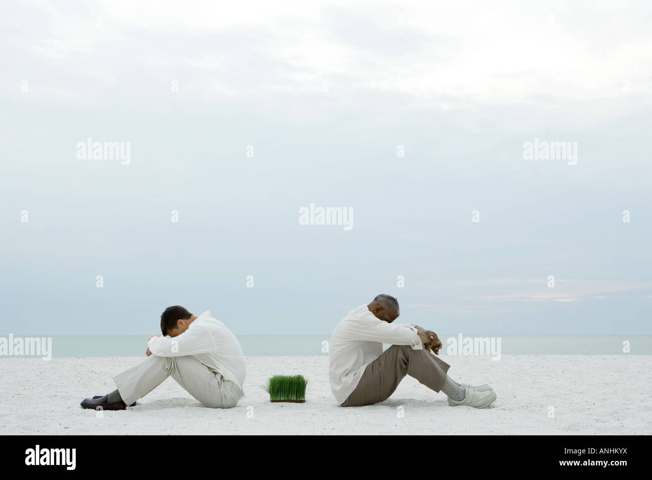 Two men sitting back to back on beach with grass between them, both with heads down - Stock Image