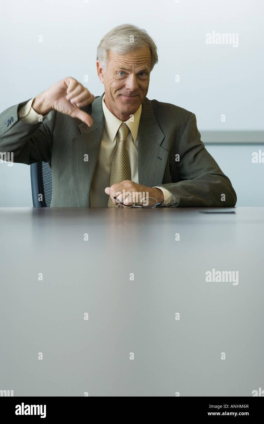 Businessman making thumbs down gesture, smiling at camera - Stock Image