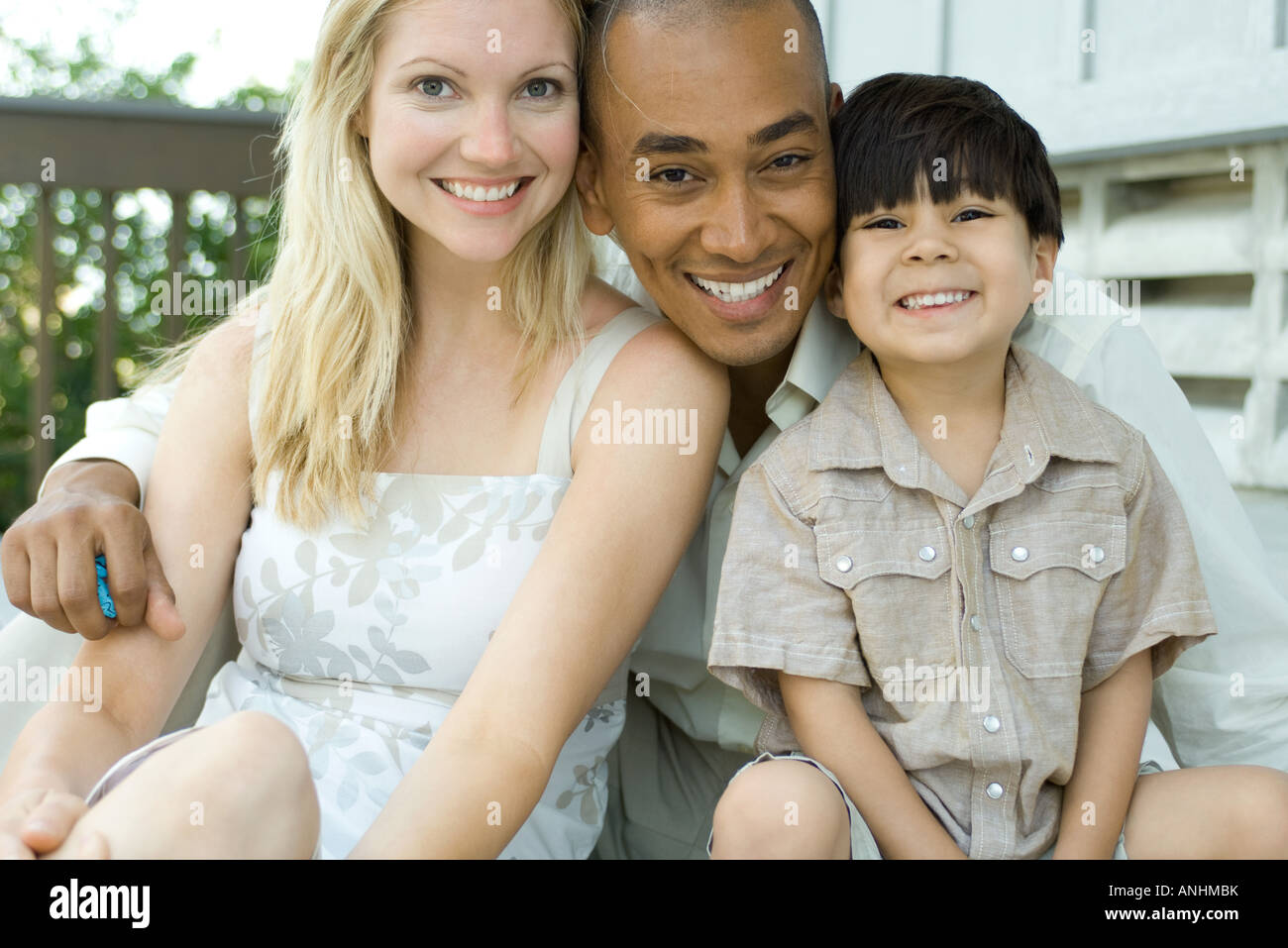 Family smiling at camera together, portrait - Stock Image