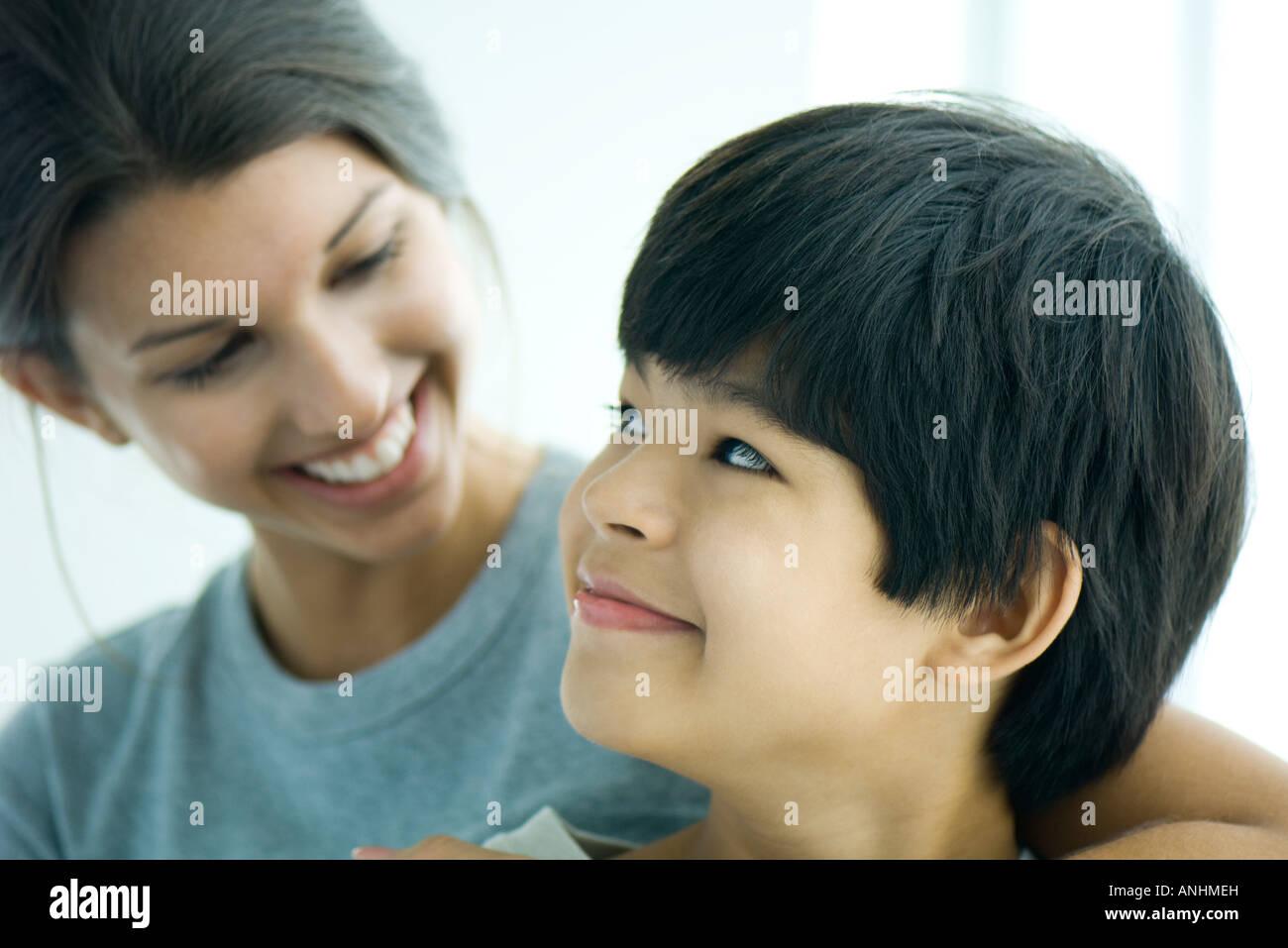 Boy looking over shoulder at sister, both smiling - Stock Image