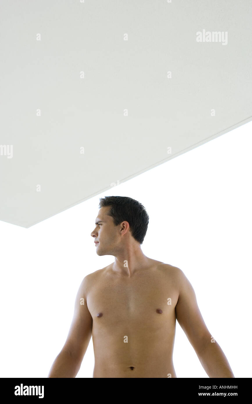 Barechested man looking away, backlit - Stock Image