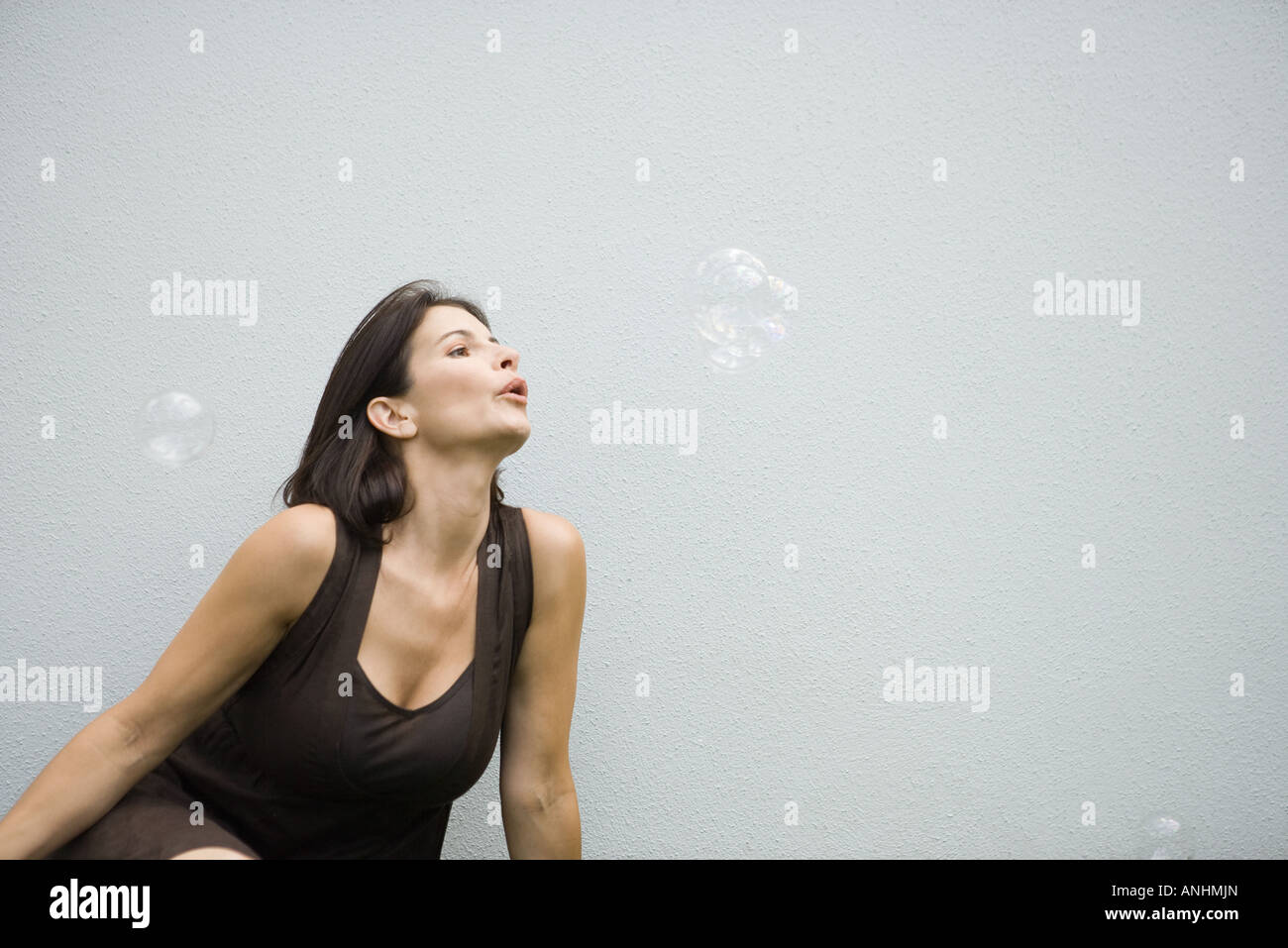 Woman blowing bubbles, waist up - Stock Image