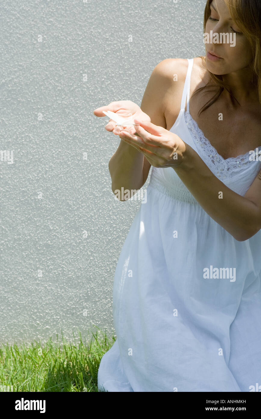 Woman in sundress holding butterfly in cupped hands Stock Photo