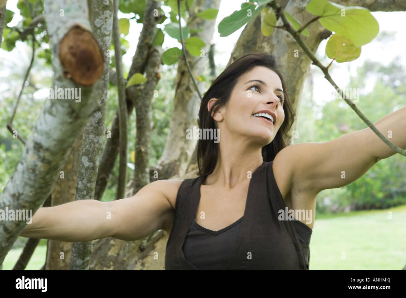 Woman among trees, smiling, looking away - Stock Image