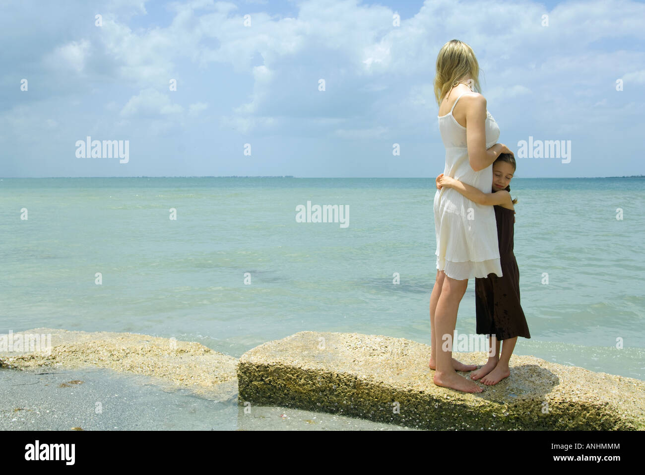 Mother and daughter standing by edge of sea, hugging, full length - Stock Image