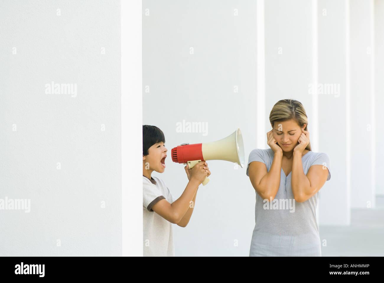 Boy screaming at mother through megaphone - Stock Image
