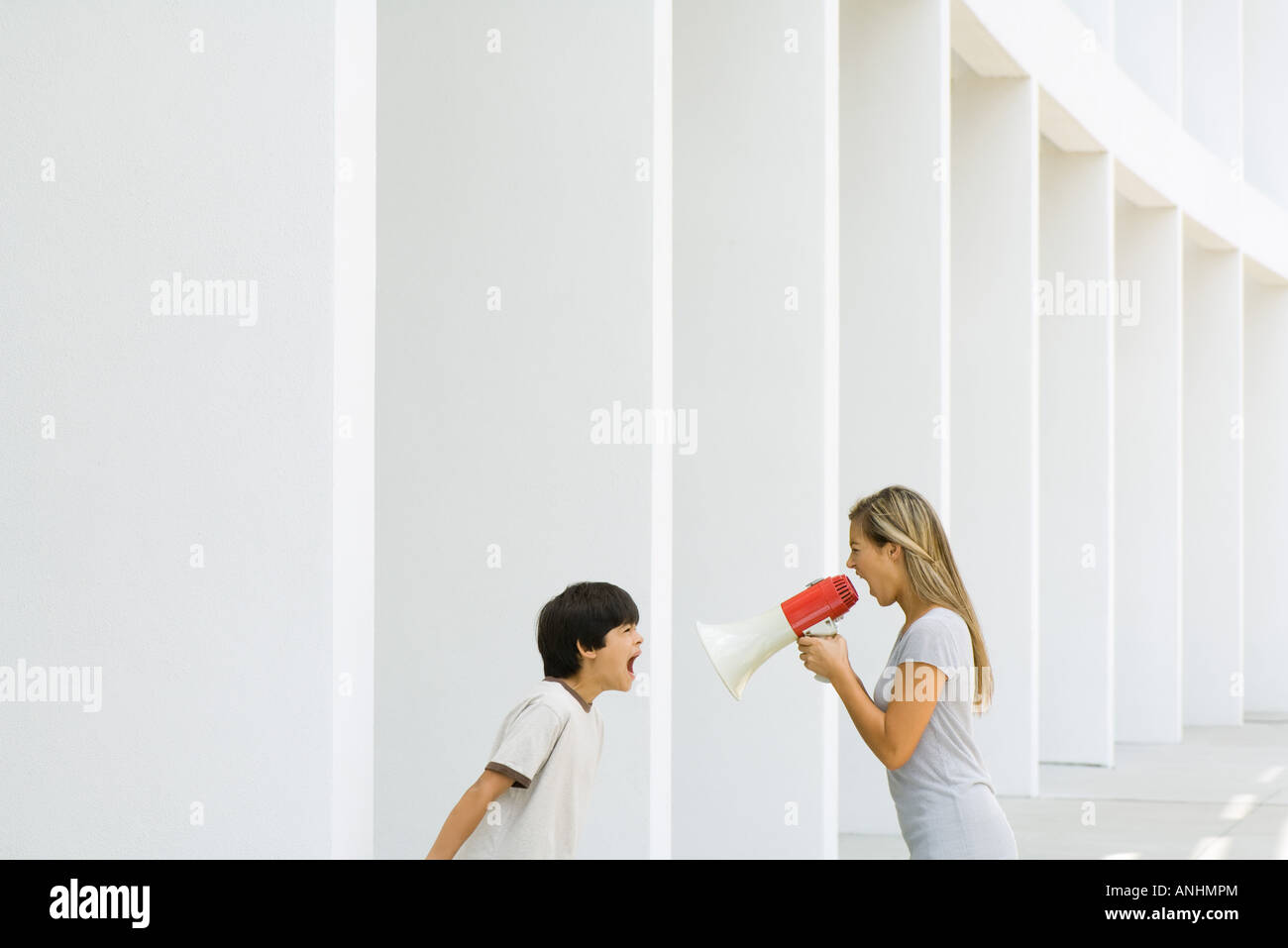 Boy and woman shouting at each other, woman using megaphone - Stock Image