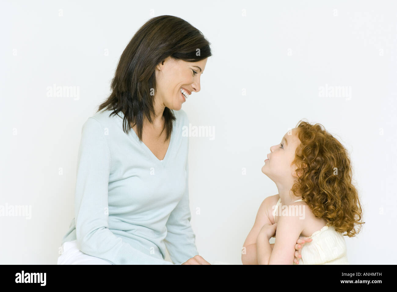 Woman and little girl having discussion, smiling - Stock Image