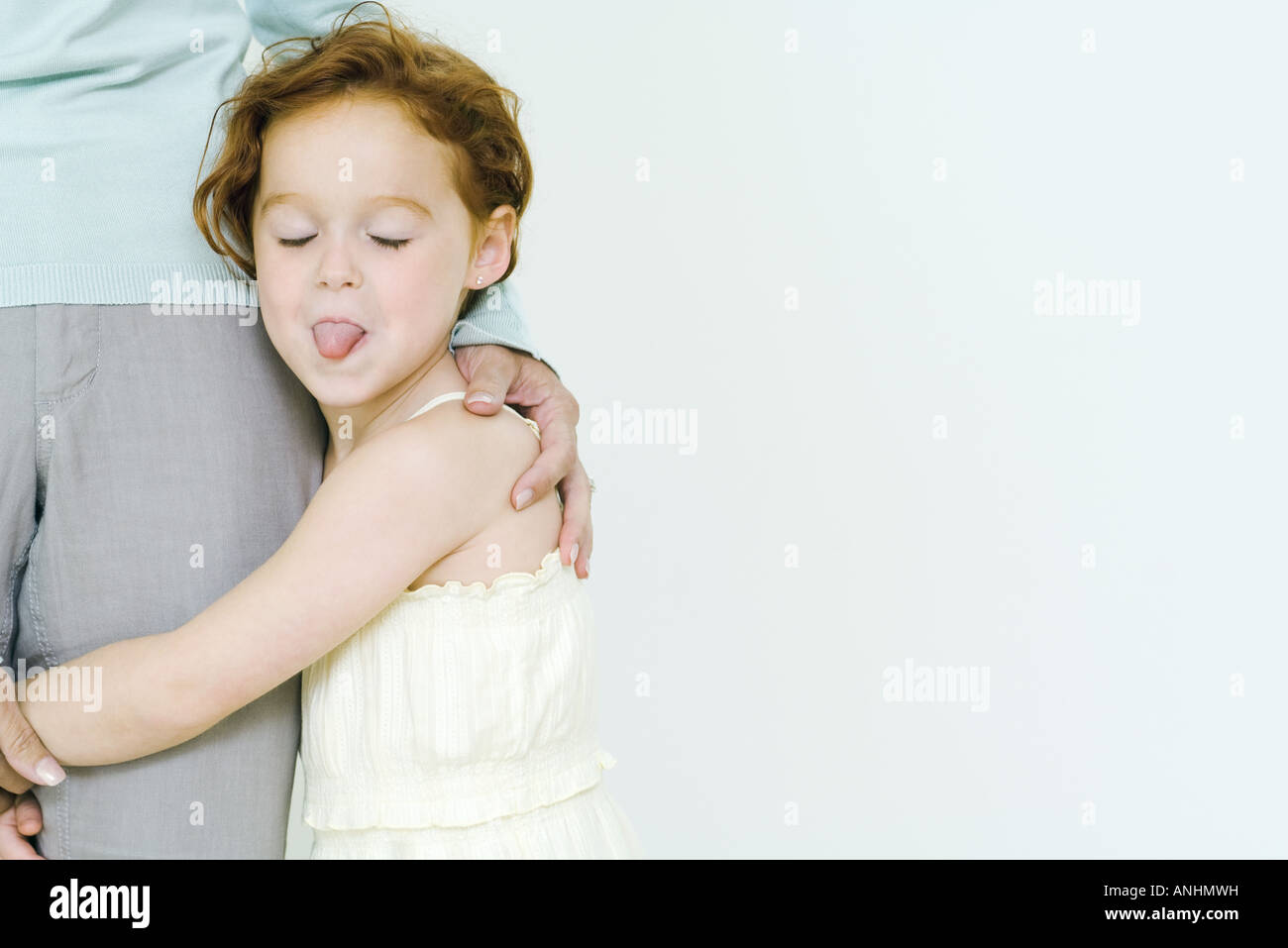Little girl holding on to mother's leg, sticking tongue out at camera - Stock Image