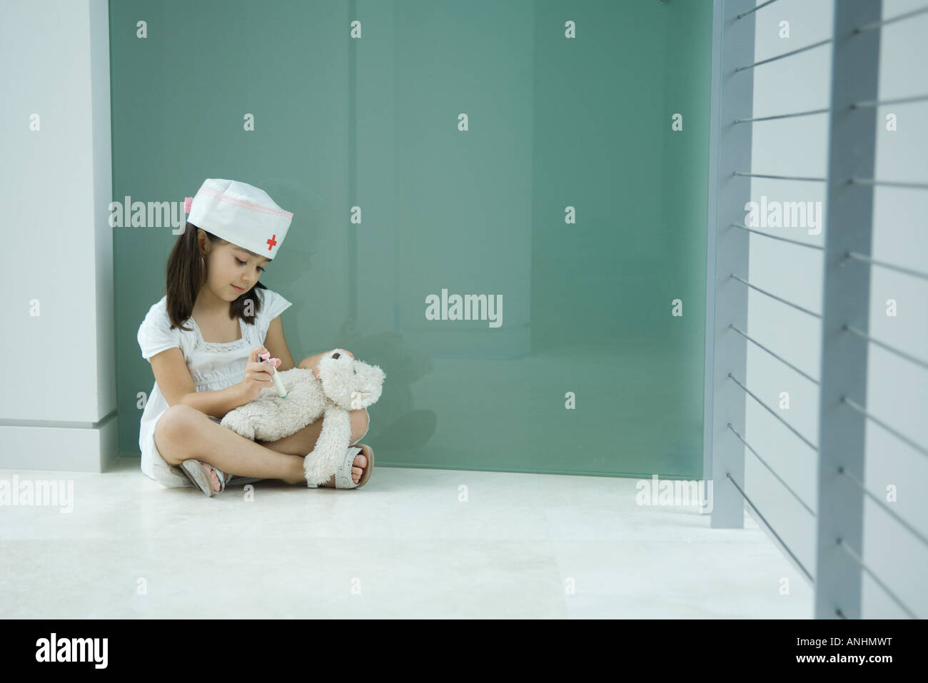 Little girl in nurse hat giving teddy bear shot - Stock Image