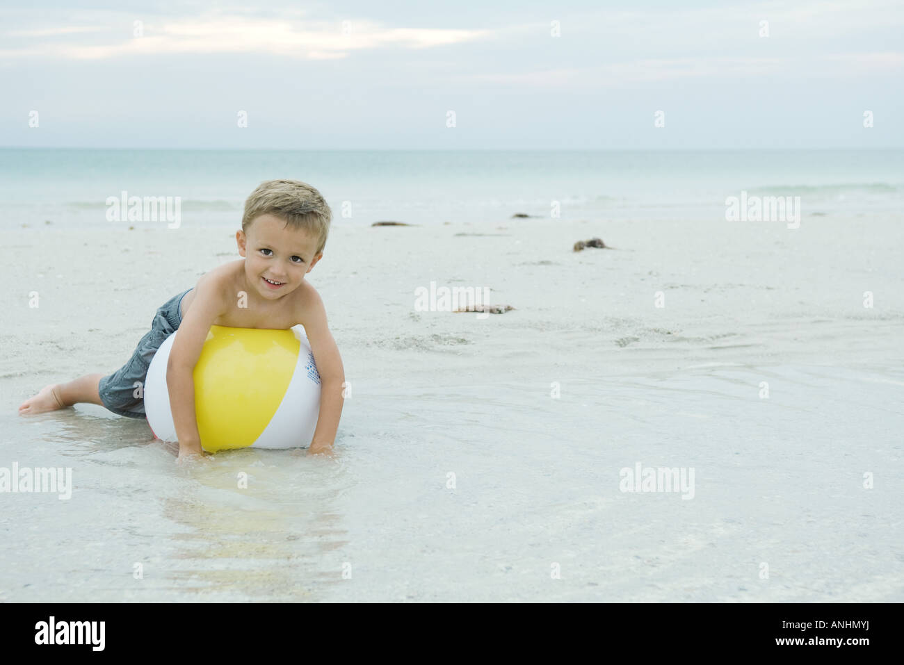 Little boy lying on beach ball, smiling at camera, full length - Stock Image