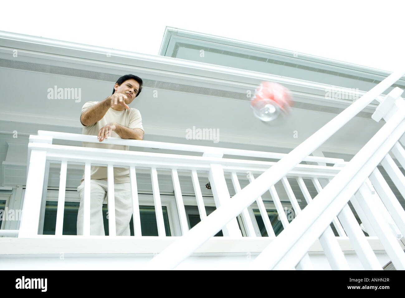 Man throwing drink can from deck, low angle view - Stock Image