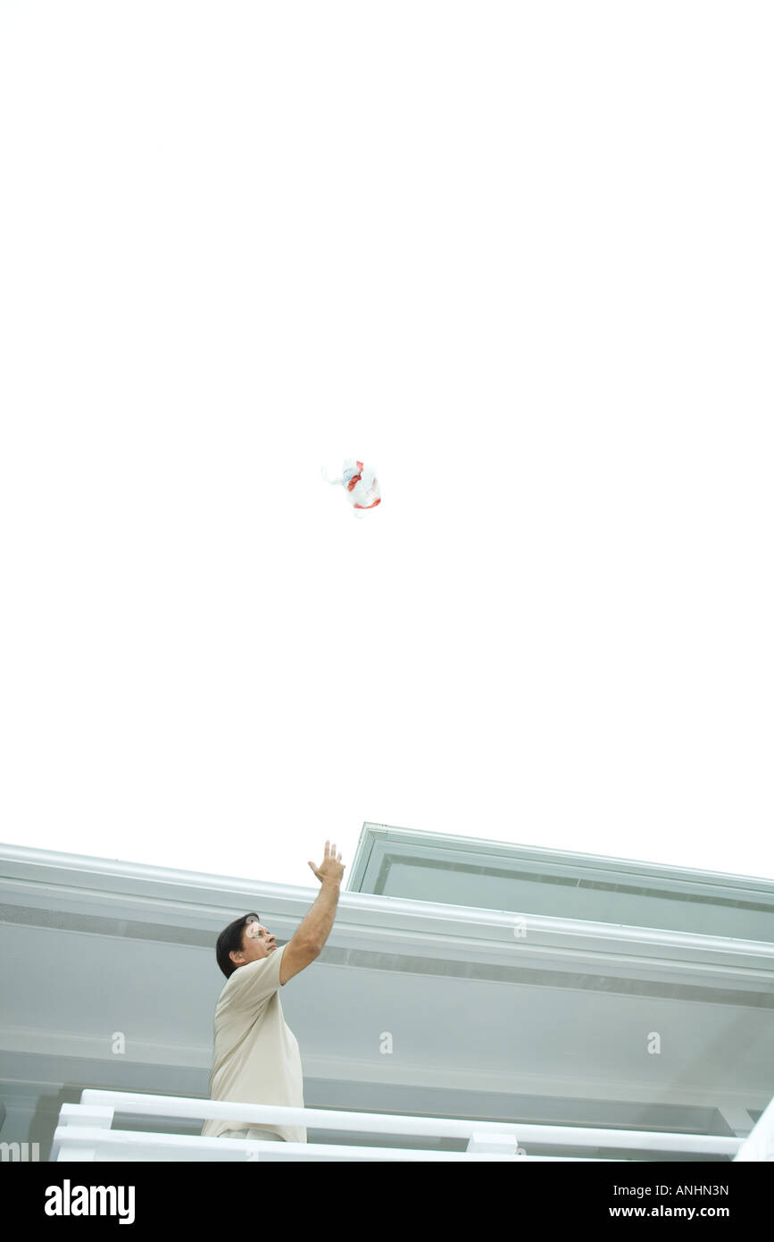 Man throwing trash into the air - Stock Image