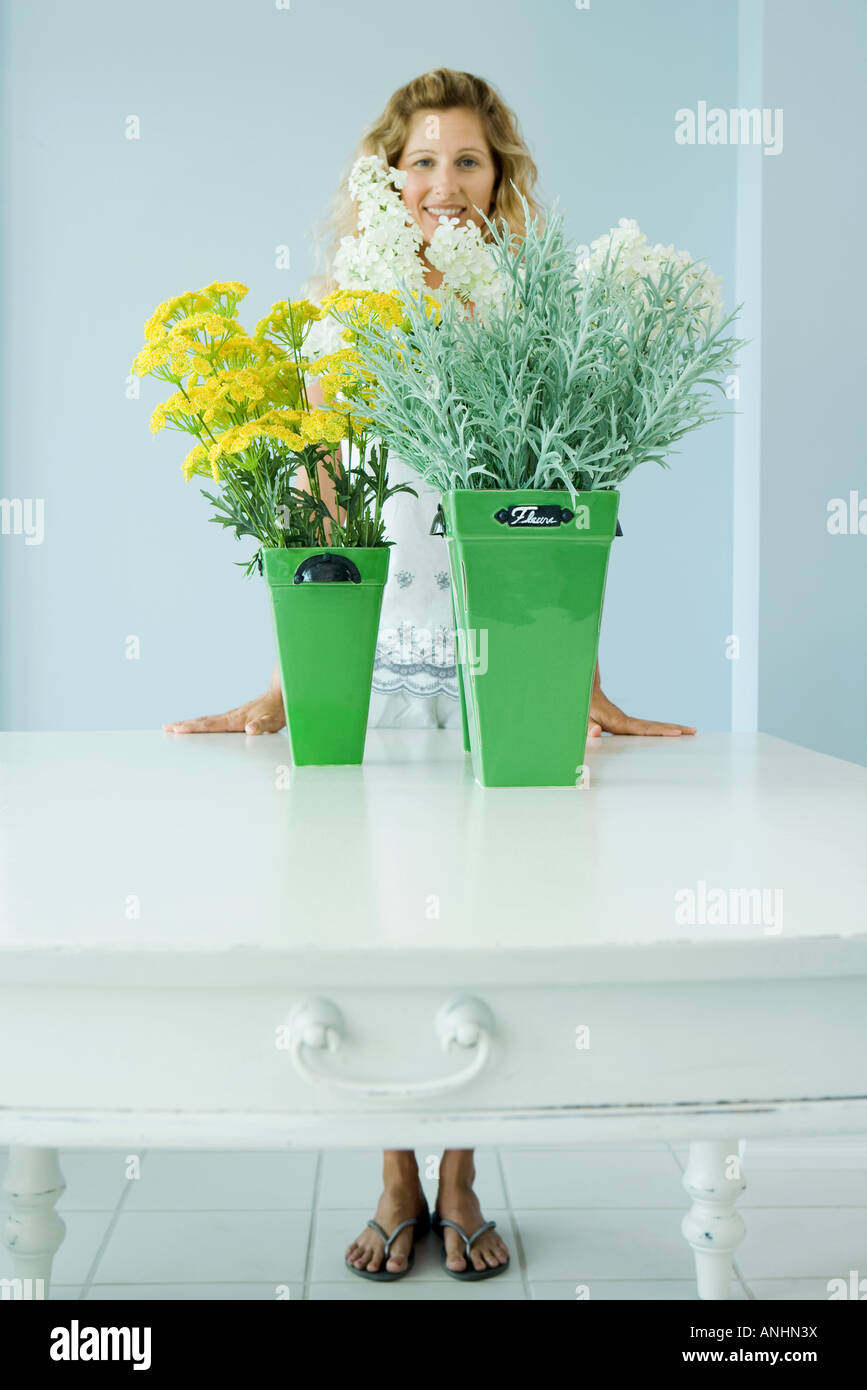 Woman standing behind cut flowers, smiling, full length - Stock Image