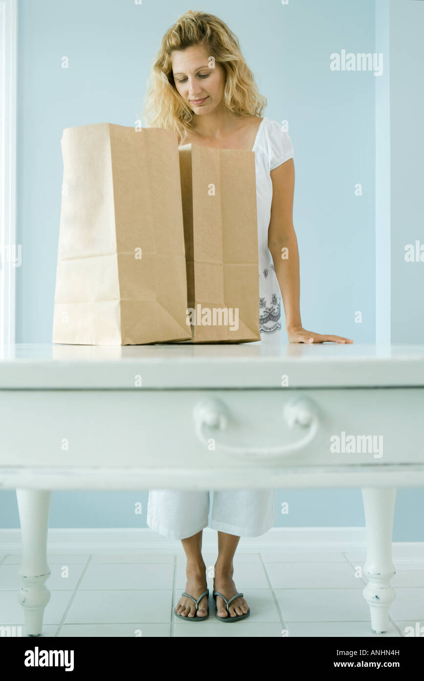 Woman looking into grocery bag - Stock Image