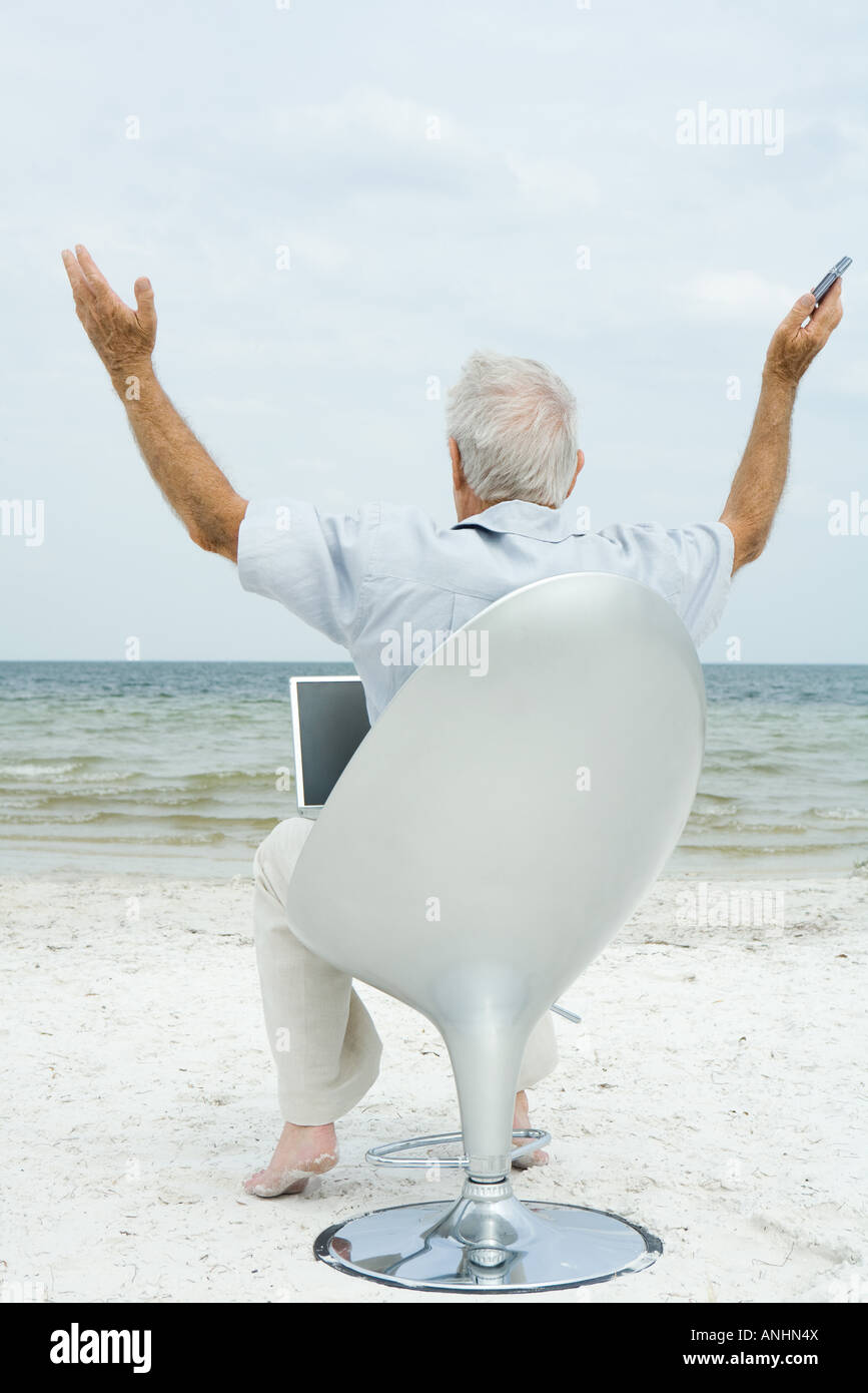 Senior man sitting in chair on beach, using laptop, arms in air, rear view - Stock Image
