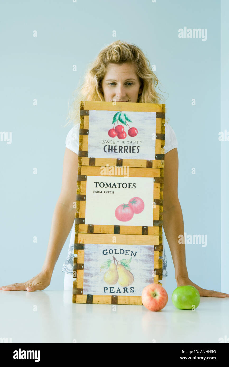 Woman standing behind crates of produce - Stock Image