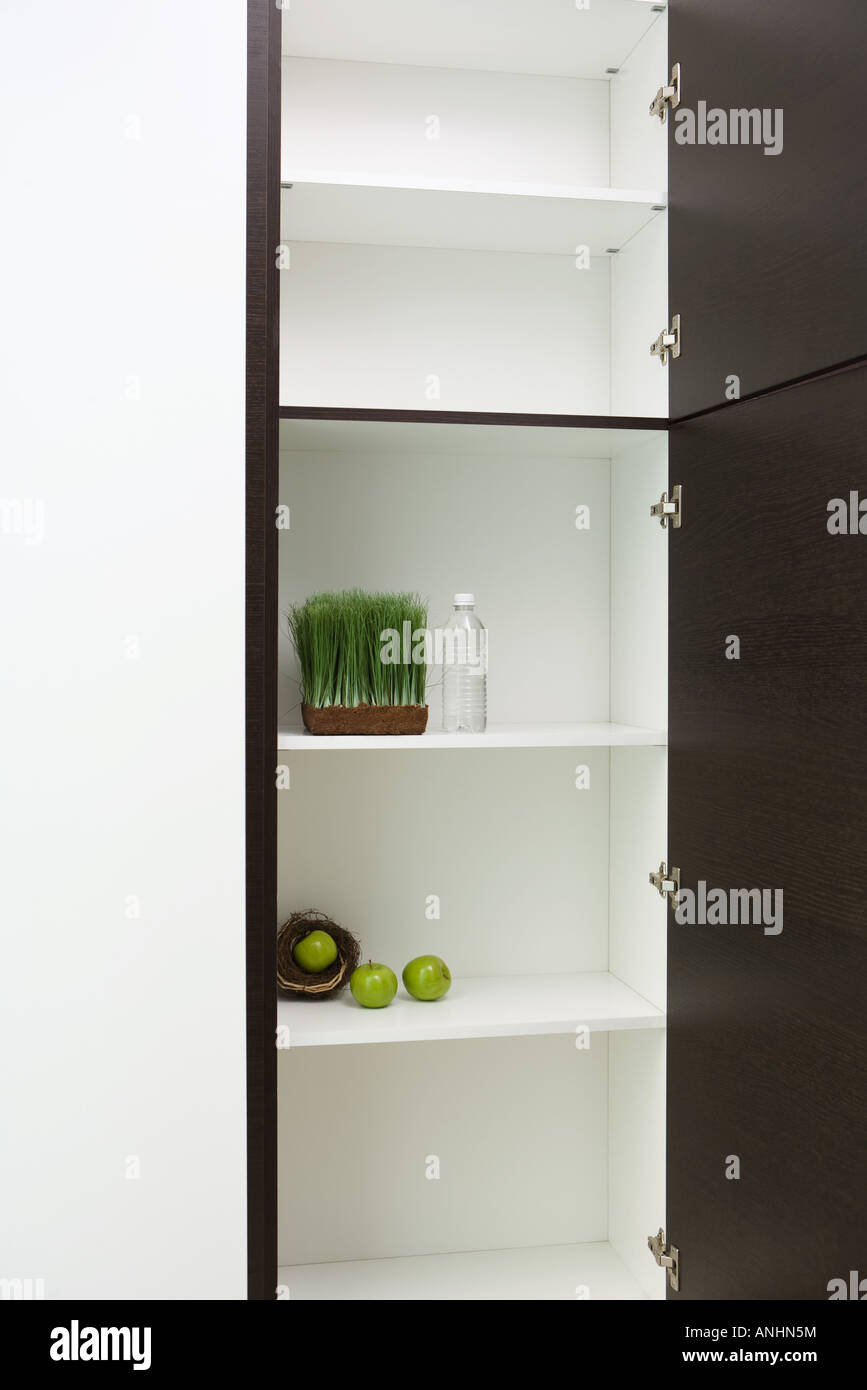 Sparse pantry containing apples in nest, tray of wheat grass and bottle of water - Stock Image