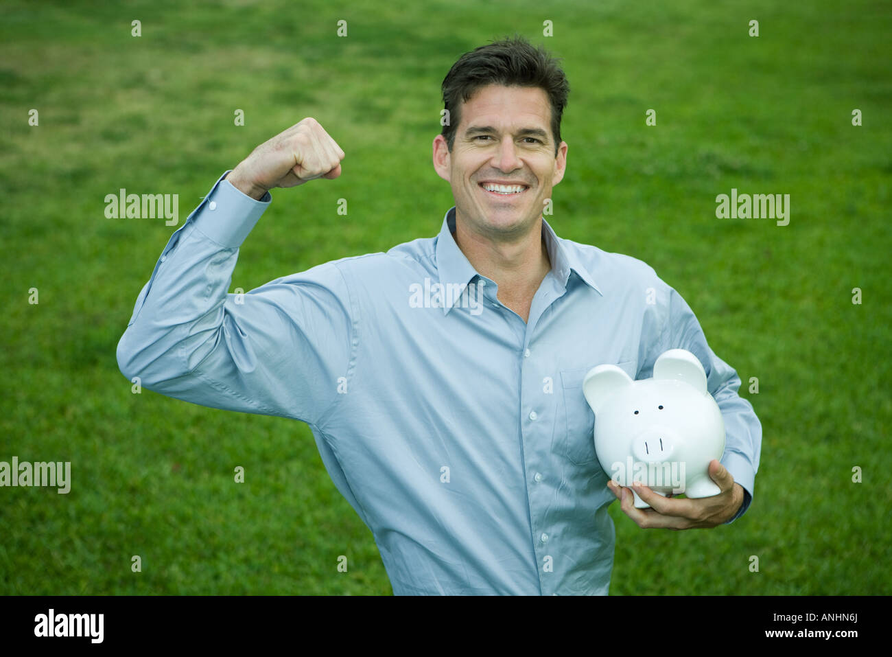 Man holding piggy bank, raising fist and smiling at camera - Stock Image