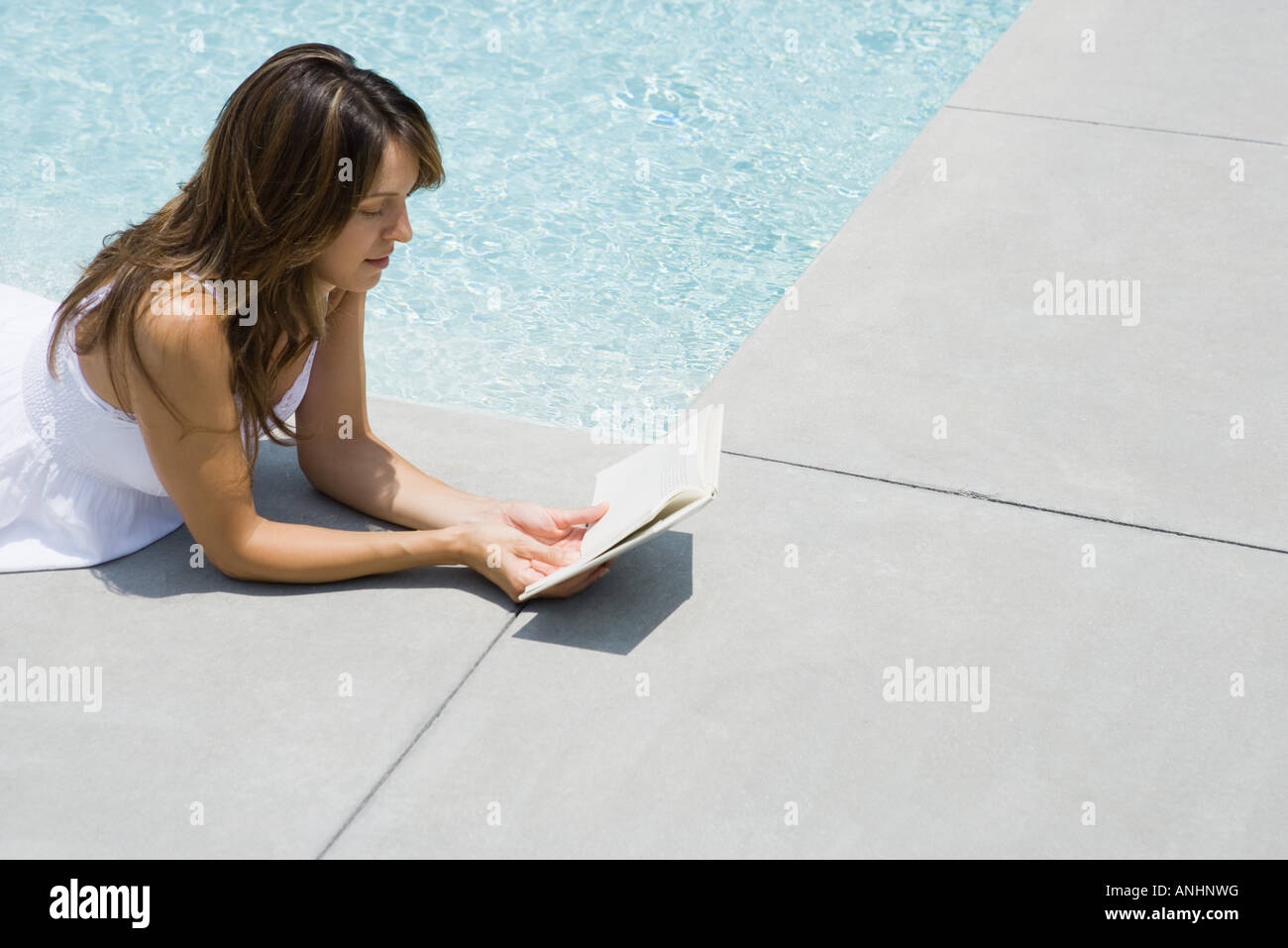 Woman lying on stomach next to pool, reading book - Stock Image