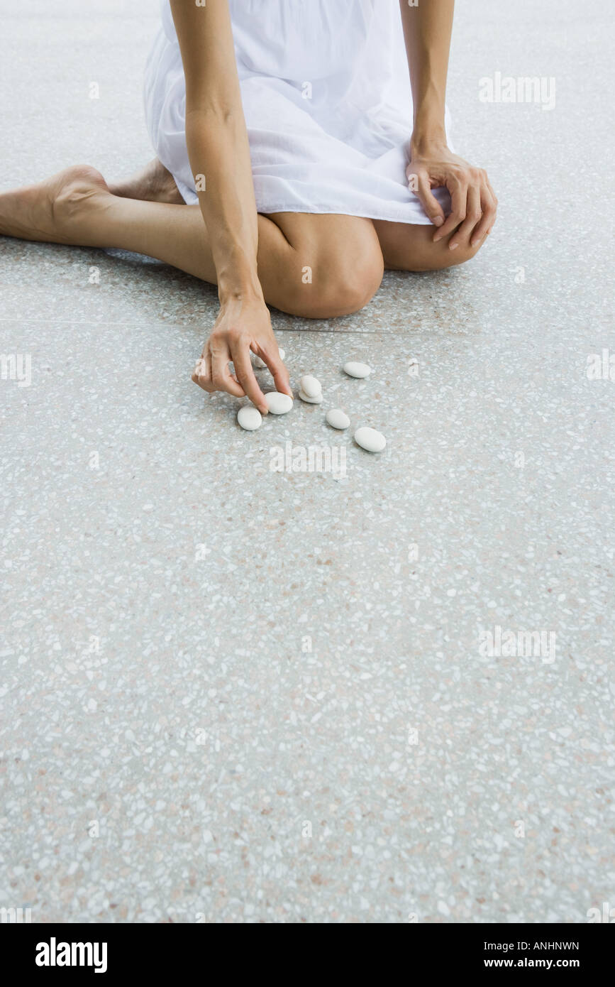 Woman kneeling on the ground arranging pebbles, cropped view Stock Photo